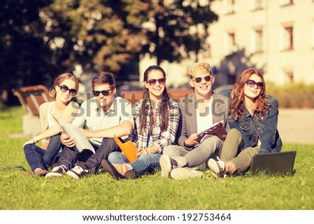 summer, internet, education, campus and teenage concept - group of students or teenagers with laptop, notebooks and folders - stock photo