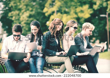 summer, internet, education, campus and teenage concept - group of students or teenagers with laptop and tablet computers hanging out - stock photo