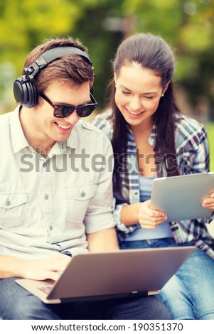 summer, internet, education, campus and teenage concept - students or teenagers with laptop and tablet computers hanging out - stock photo
