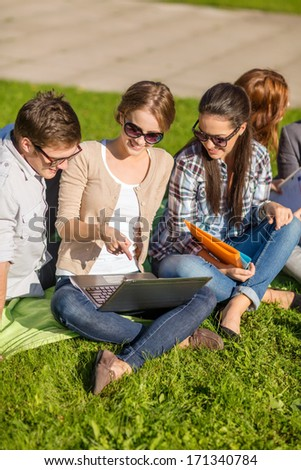 summer, internet, education, technlogy and campus concept - group of students or teenagers with laptop, notebooks, files and folders - stock photo