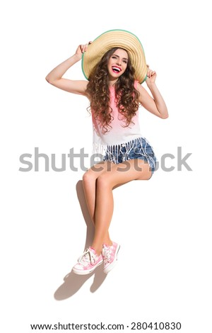 Summer Is Coming. Smiling sexy young woman in straw hat, pink top, jeans shorts and pink sneakers sitting on the white banner. Full length studio shot isolated on white. - stock photo