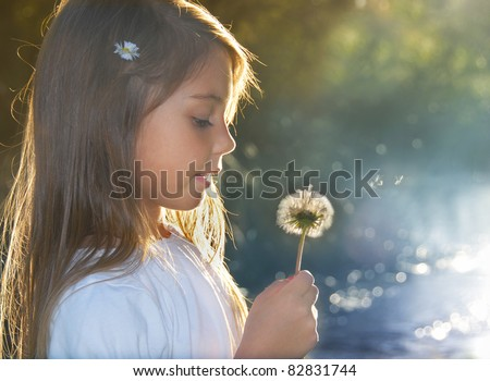 Summer joy, little girl blowing dandelion at sunset near the river - stock photo