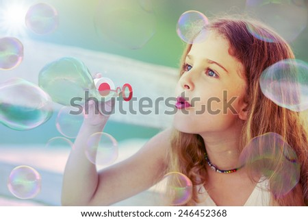 Summer joy - lovely girl playing with soap bubbles, filtered
