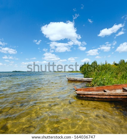 Summer lake view with wooden boats near shore.