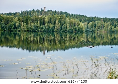 Summer landscape at Aulanko nature park in Finland. Reflection of the scene and the lookout tower in the still water of the lake