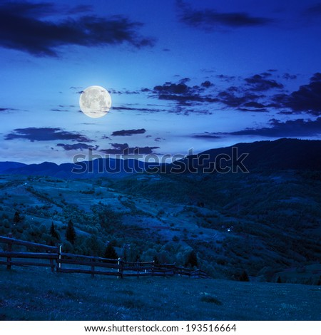 summer landscape. fence near the meadow on hillside. forest in fog on the mountain at night in moon light - stock photo