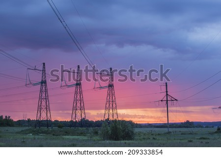 summer landscape high voltage power lines on sunrise background in the field near the woods - stock photo