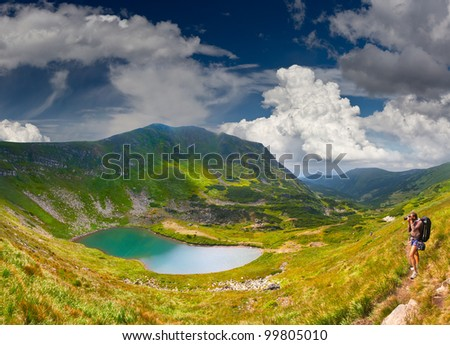 Summer landscape in the mountains near the lake with photographer - stock photo