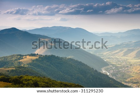 Summer landscape in the mountains. View of the forested hills and the river winding through the village in the valley. - stock photo