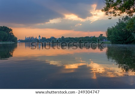 Summer landscape in the pond in the park at sunset through the clouds. Izmailovo Park and the Kremlin, Moscow, Russia