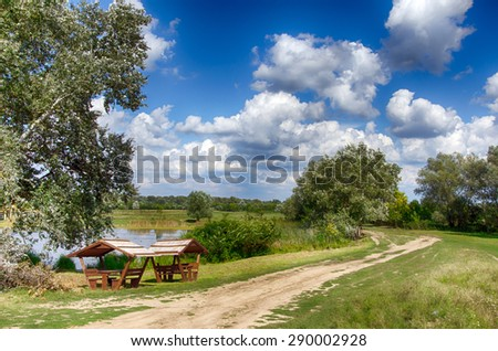 Summer landscape - lake, dirt road, bench,tree,bush, blue sky and clouds. The place is one of the backwaters of the Tisza river in Tiszalok, Hungary. - stock photo