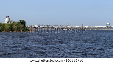 summer landscape of a sunny day on the river, the lighthouse and the dam on the horizon - stock photo