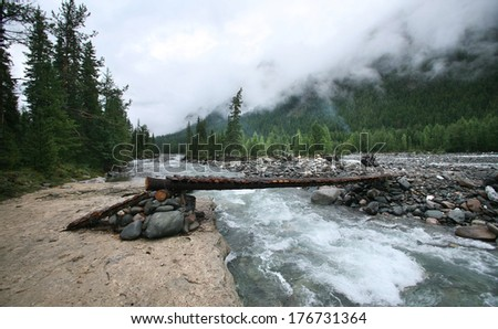 summer landscape of a wooden bridge across the mountain river, pine forests and clouds