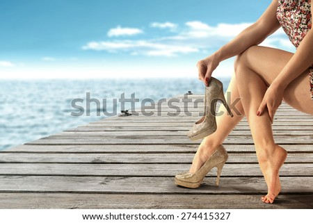 summer landscape of sea and wooden old pier and woman legs