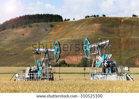 summer landscape oil pumps in a field on a clear sunny day - stock photo