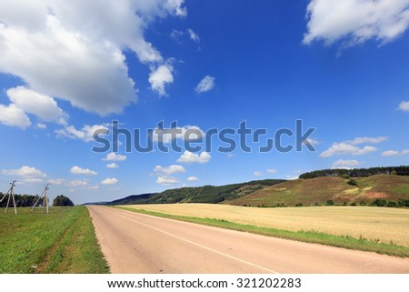 summer landscape road in a field in the hills on a sunny day