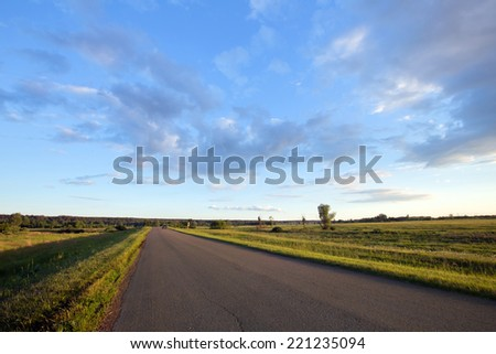 summer landscape road to the horizon at sunset and dramatic clouds on a blue sky