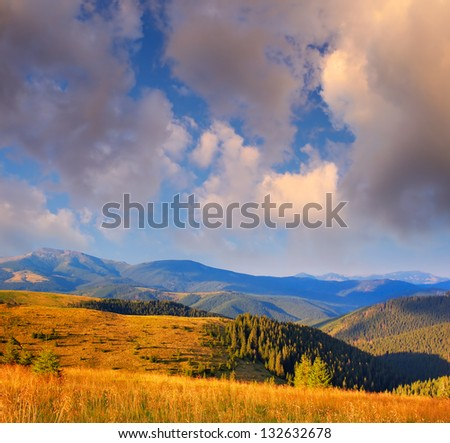 Summer landscape with a cloudy sky over the mountains - stock photo