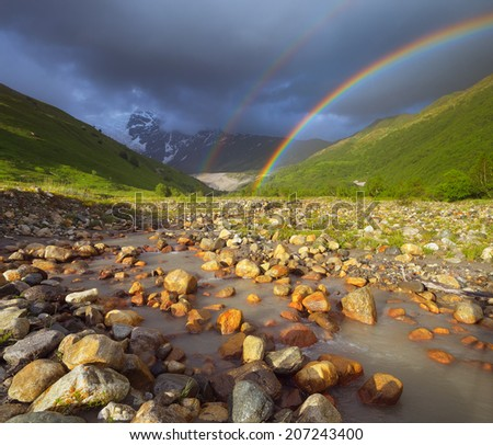 Summer landscape with a rainbow in the mountains above the river. Zemo Svaneti, Georgia - stock photo