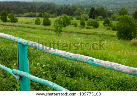 summer landscape with an old wooden fence in the foreground - stock photo