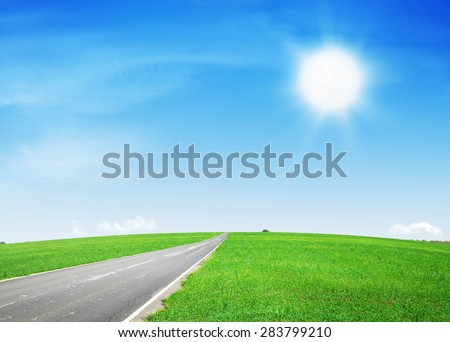 Summer landscape with asphalt road through the green field and blue sky - stock photo