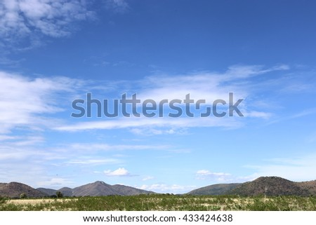 summer landscape with cultivated lands mountains and white clouds - stock photo