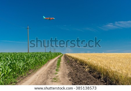 Summer landscape with earth road and landing aircraft over agricultural fields in Ukraine
