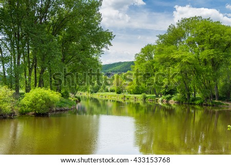 Summer landscape with green grass, road, river and clouds