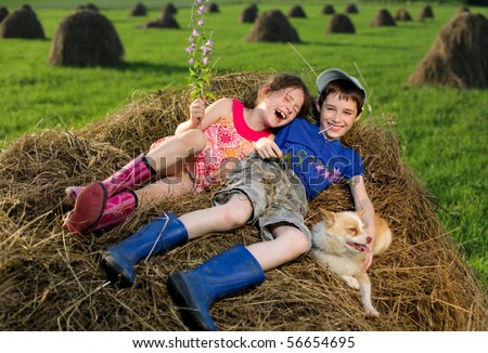 Summer landscape with hay cocks, couple children sitting on large hay