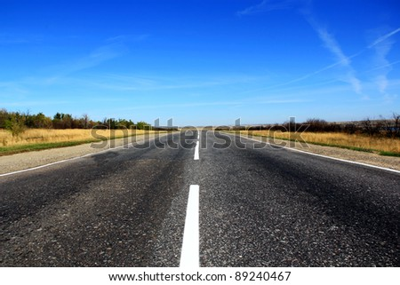 Summer landscape with line of road and blue sky