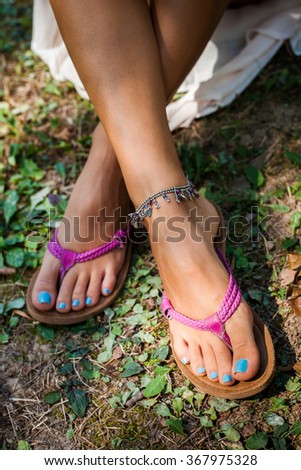 summer leather flip flops and ankle bracelet, outdoor shot from above on grass, shallow depth of field - stock photo