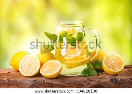 Summer lemon drink on a wooden table - stock photo