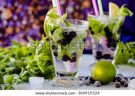 Summer lemonade mojito with lime, blackcurrant and mint - stock photo