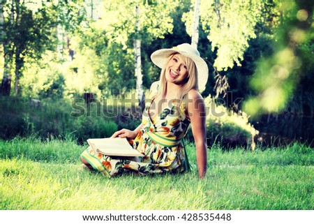 Summer lifestyle concept. Blonde young woman girl with hat relaxing in a park reading book, sitting alone on grass. Sunny day - stock photo