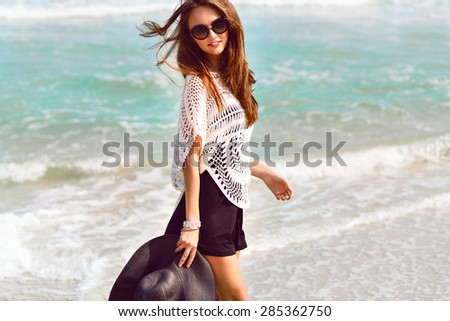 Summer lifestyle fashion portrait of young woman in stylish outfit holding hat and walking near ocean, positive mood, vintage toned colors. - stock photo