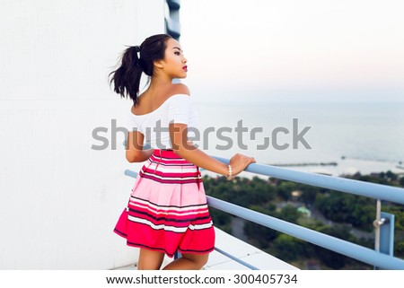 Summer lifestyle  image of pretty cute asian girl posing outdoor wearing  summer  bright  hipster outfit. White crop top and  striped  red skirt.  Bright toned colors. - stock photo