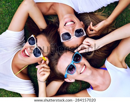 Summer lifestyle portrait of three hipster woman laying on the grass enjoy nice day, wearing white simple tops and bright sunglasses. Best friends girls having fun, joy, playful mood. - stock photo