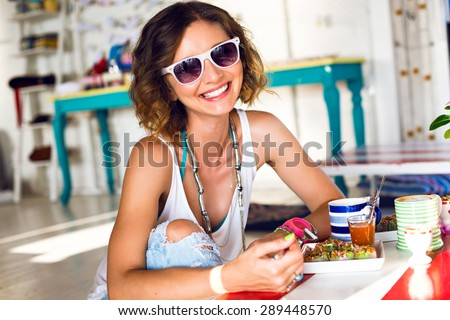 Summer lifestyle portrait of woman taking tasty lunch and drinking cappuccino, wearing hipster outfit and sunglasses, smiling,having fun in cafe, sunny colors, trendy clothes. - stock photo