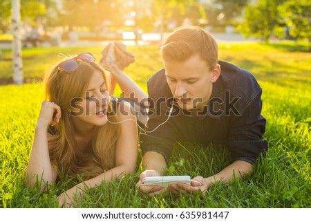 summer, love and people concept - close up of happy teenage couple lying on grass with earphones and listening to music.