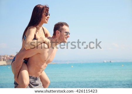 summer love - young woman on the back of her boyfriend