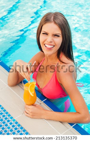 Summer makes me crazy! Playful young woman in bikini holding cocktail and showing her tongue while standing at the pool