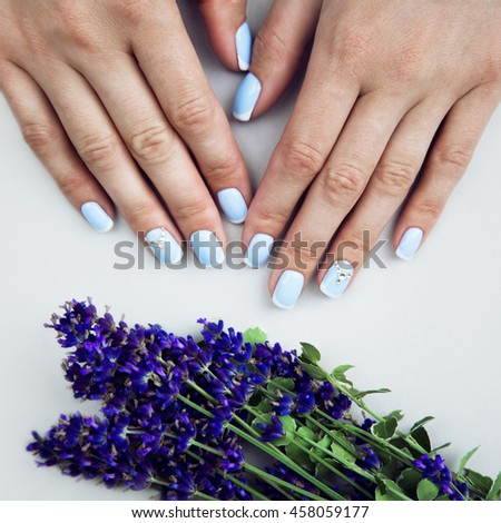 Summer manicure for the bride in gentle tones with lavender flowers. Nail Design. Close-up.