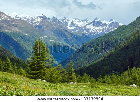 Summer mountain cloudy landscape with snow on mount top (Alps, Switzerland)