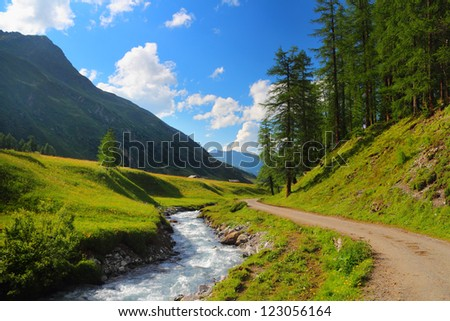 Summer mountain landscape and green meadow with stream in the foreground, Sertig Dorfli, Davos, Switzerland - stock photo