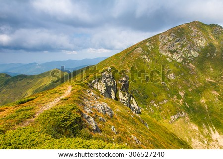Summer mountain landscape at sunshine. Hiking trail in the hills. - stock photo