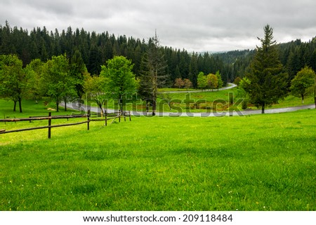 summer mountain landscape. curve asphalt road and wooden fence near the meadow on hillside with forest - stock photo