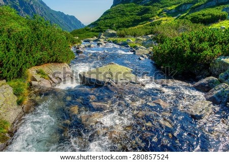 Summer mountain landscape. Picturesque view stretches over stream with big stones in the Five Pond Valley in Tatra mountains, Poland. - stock photo