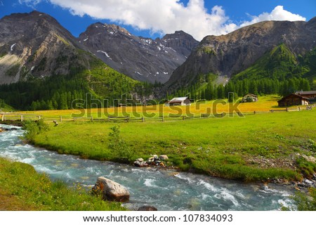 Summer mountain landscape with chalet on a meadow and stream in foreground, Sertig Dorfli, Davos, Switzerland