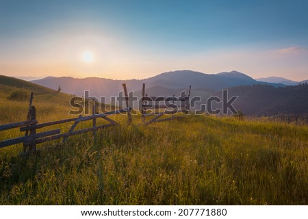 Summer mountain landscape with old farm fence.  - stock photo