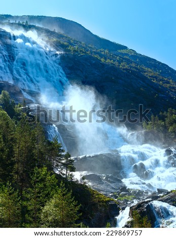 Summer mountain  Langfossen waterfall on slope (Etne, Norway).